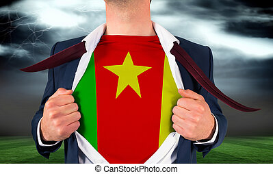 Businessman opening shirt to reveal cameroon flag against football pitch under stormy sky
