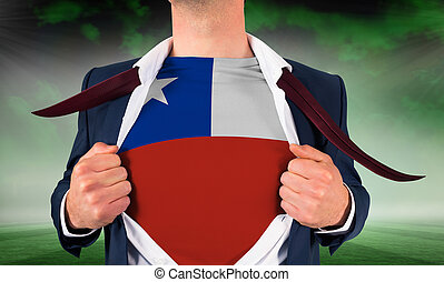 Businessman opening shirt to reveal chile flag against football pitch under green sky
