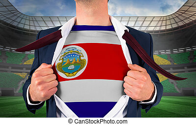 Businessman opening shirt to reveal costa rica flag against large football stadium with brasilian fans