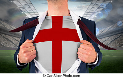 Businessman opening shirt to reveal england flag against large football stadium with lights