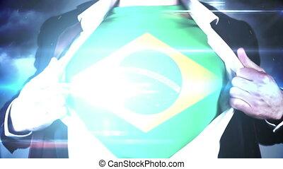 Businessman opening shirt to reveal brazil flag on black...