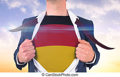 Businessman opening shirt to reveal germany flag against beautiful orange and blue sky