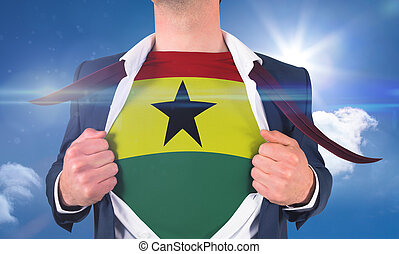 Businessman opening shirt to reveal ghana flag against bright blue sky with clouds