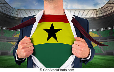 Businessman opening shirt to reveal ghana flag against large football stadium with brasilian fans