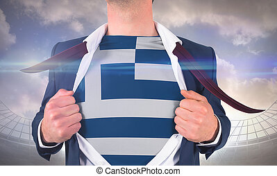 Businessman opening shirt to reveal greece flag against large football stadium under cloudy blue sky