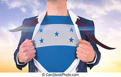 Businessman opening shirt to reveal honduras flag against beautiful orange and blue sky