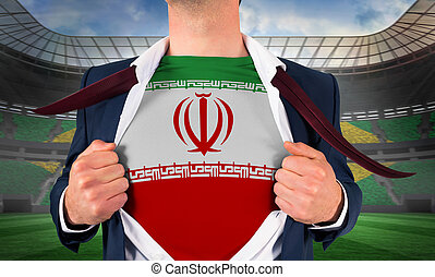Businessman opening shirt to reveal iran flag against large football stadium with brasilian fans