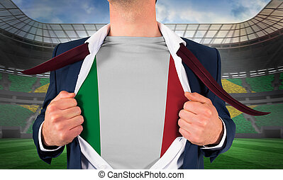 Businessman opening shirt to reveal italy flag against large football stadium with brasilian fans