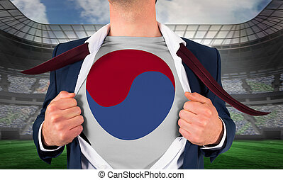 Businessman opening shirt to reveal korea republic flag against large football stadium under spotlights