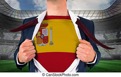 Businessman opening shirt to reveal spain flag against large football stadium under spotlights