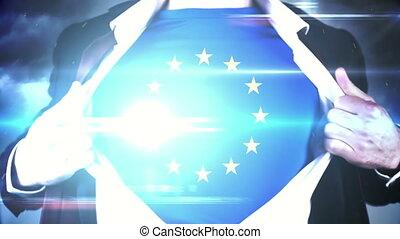 Businessman opening shirt to reveal EU flag on black...