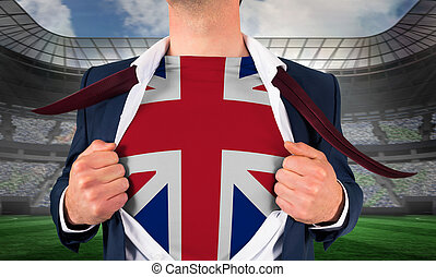Businessman opening shirt to reveal union jack flag against large football stadium under spotlights
