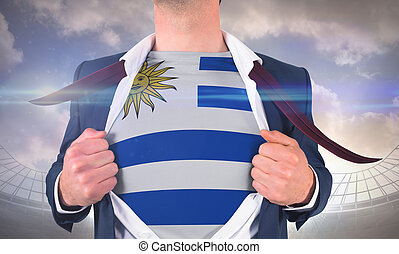 Businessman opening shirt to reveal uruguay flag against large football stadium under cloudy blue sky