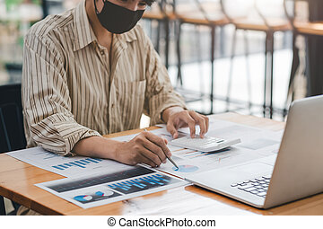 Businessman or accountant wear mask working on desk office with using a calculator to calculate the numbers, finance accounting concept