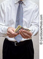 Businessman, or politician, counting a Dollar banknotes bribe for corruption