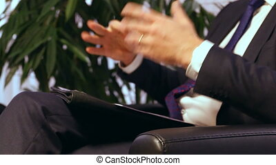 Businessman or politician giving live interview. Body language gesticulation with hands. Close up shot.
