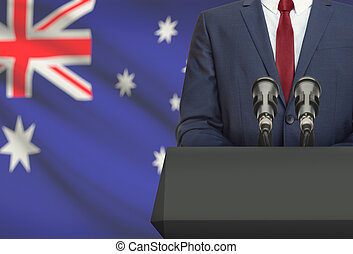 Businessman or politician making speech from behind a pulpit with national flag on background - Australia