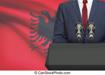 Businessman or politician making speech from behind a pulpit with national flag on background - Albania