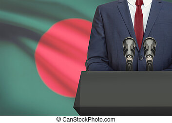 Businessman or politician making speech from behind a pulpit with national flag on background - Bangladesh