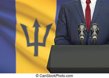 Businessman or politician making speech from behind a pulpit with national flag on background - Barbados