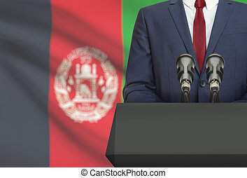 Businessman or politician making speech from behind a pulpit with national flag on background - Afghanistan
