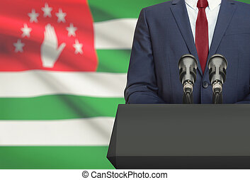 Businessman or politician making speech from behind a pulpit with national flag on background - Abkhazia