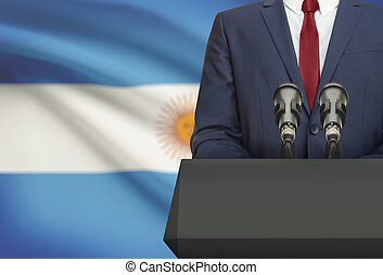 Businessman or politician making speech from behind a pulpit with national flag on background - Argentina