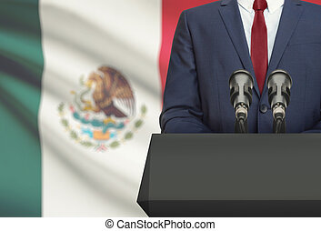 Businessman or politician making speech from behind the pulpit with national flag on background - Mexico