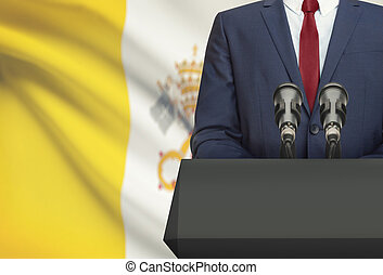 Businessman or politician making speech from behind a pulpit with national flag on background - Vatican City State