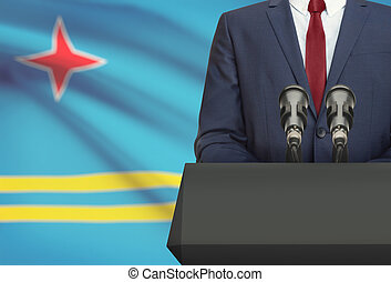Businessman or politician making speech from behind a pulpit with national flag on background - Aruba