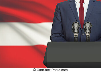 Businessman or politician making speech from behind a pulpit with national flag on background - Austria