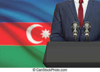 Businessman or politician making speech from behind a pulpit with national flag on background - Azerbaijan