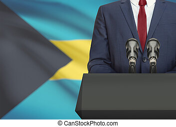 Businessman or politician making speech from behind a pulpit with national flag on background - Bahamas