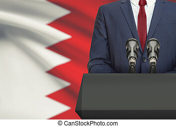 Businessman or politician making speech from behind a pulpit with national flag on background - Bahrain