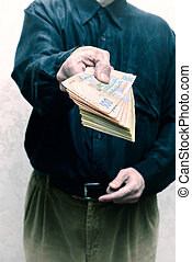 Businessman, or politician, offering a Hryvnia banknotes bribe for corruption, in Ukraine