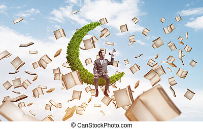 Businessman or student announcing something in loudspeaker and books flying around