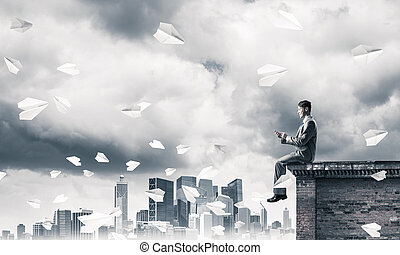 Businessman or student on roof edge making calls and cityscape a