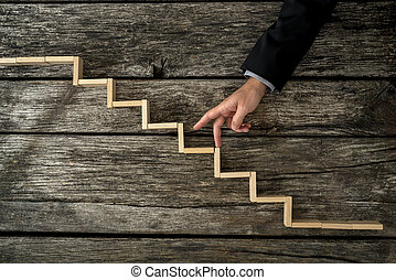 Businessman or student walking his fingers up wooden steps ...