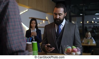 Businessman ordering while using cellphone at cafe