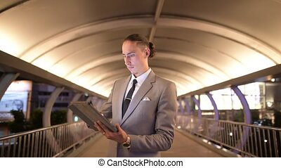 Businessman Outdoors At Night Using Digital Tablet