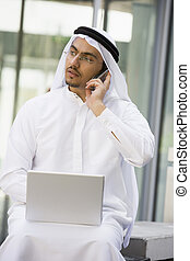 Businessman outdoors with laptop using cellular phone by...