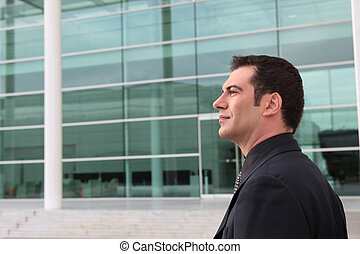 Businessman outside a glass fronted building