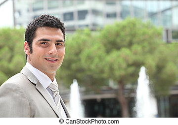 Businessman outside an office building with fountains