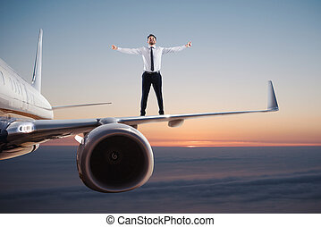 Businessman over an airplane swing. Concept of freedom