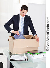 Businessman Packing Files In Cardboard Box In Office - Sad...