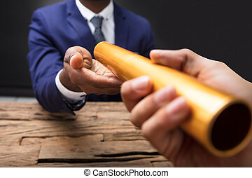 Businessman Passing Baton To His Partner