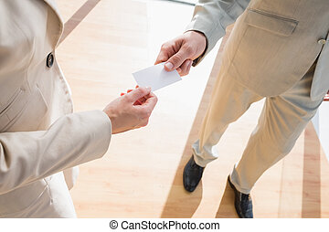 Businessman passing his card to businesswoman