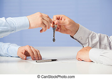 Businessman passing keys to his partner