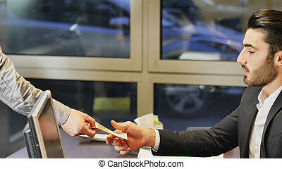 Businessman paying cash money to other man