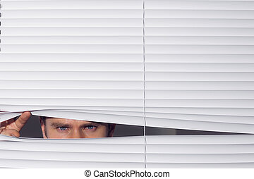 Businessman peeking through blinds - Close up portrait of a ...